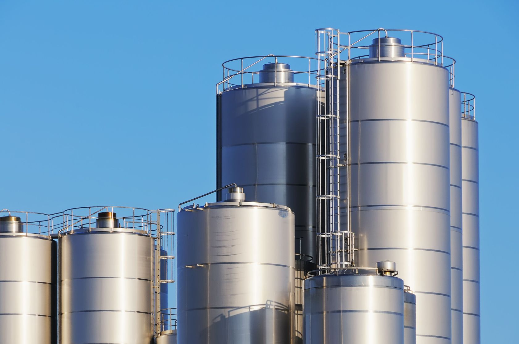 6604435 - close up shot of storage tanks of dairy plant against blue sky.